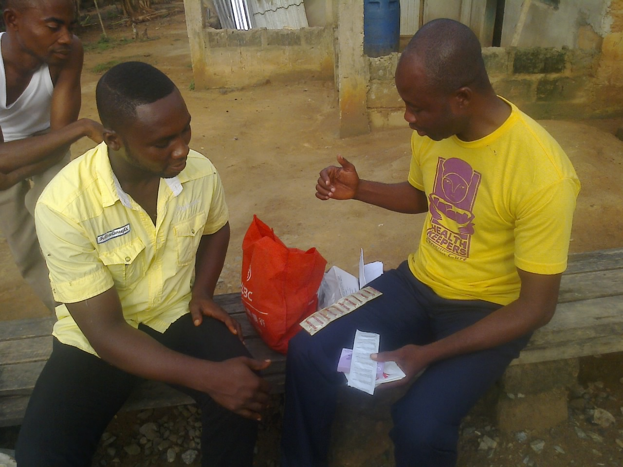 Photo of Nana Akorlegah educating his male colleagues in his community on the use of condoms.