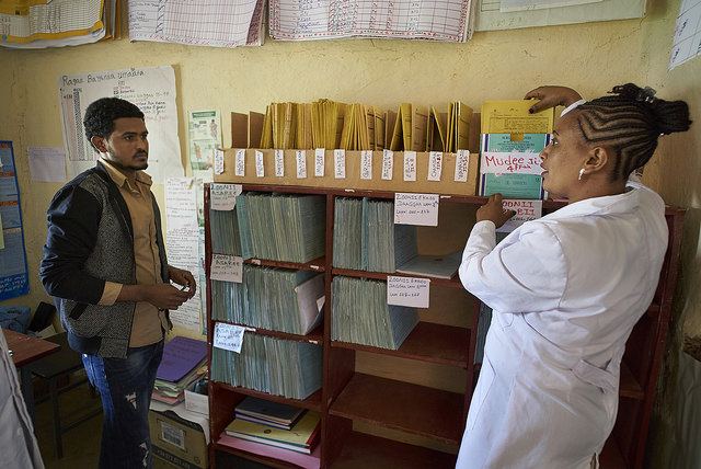 Mekdes explains the Tickler file box to Tesfu, a zonal health department employee.
