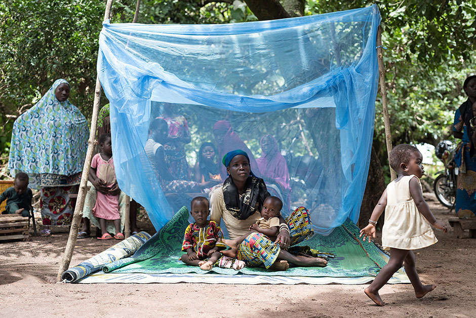 Photo of a woman holding two small children underneath a bednet, with a child walking by and villagers in the background.