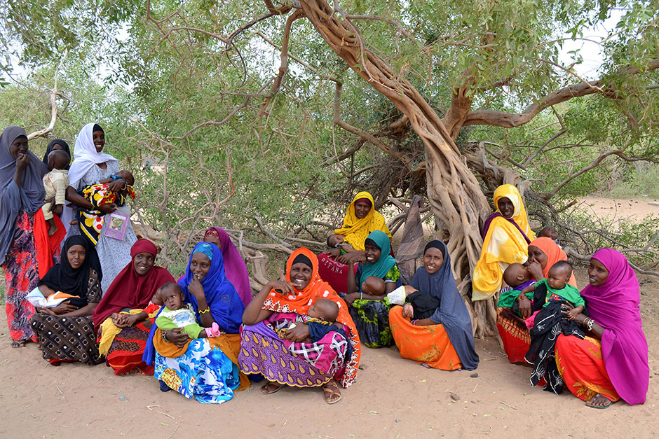 Photo of a group of women seated around a tree, holding their infants.