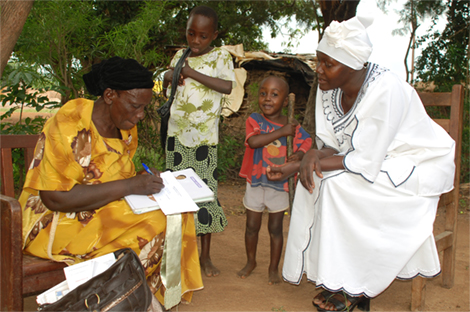 Photo of a female health worker talking to a seated woman with two children