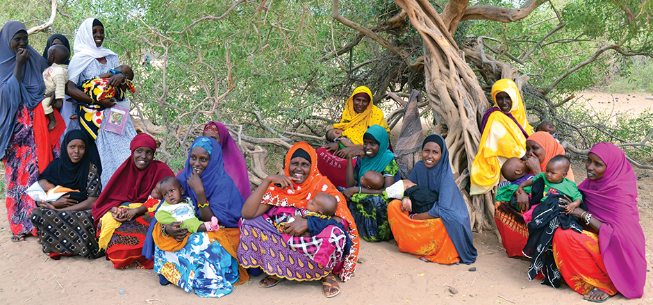 Photo of several women sitting under a tree with infants