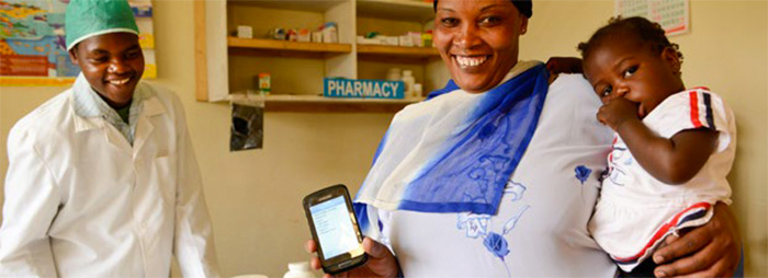 Photo of a woman at a health clinic holding a smartphone and an infant. Source: Elmvh/GFDL via Wikimedia Commons