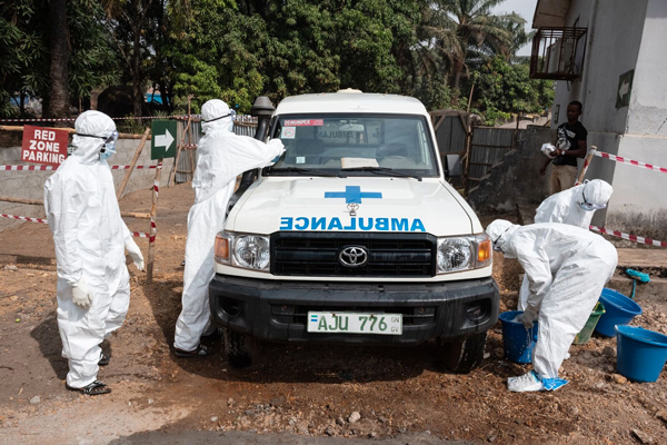 Photo of men in PPE suits washing an ambulance during a training in Sierra Leone. Credit: Joshua Yospyn