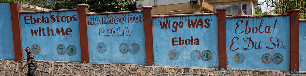 Photo showing 'Ebola Stops With Me' in different languages on a roadside.