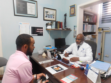 Photo of Williams speaking with a doctor across a desk.
