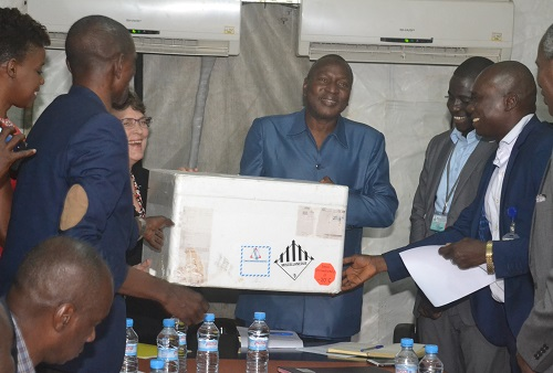 USAID Mission Director Barbara Dickerson (third from left) presents a box of laboratory supplies to Dr. Sakoba Keita, Director General of the National Agency for Health Security, on behalf of Guinea's Ministry of Health