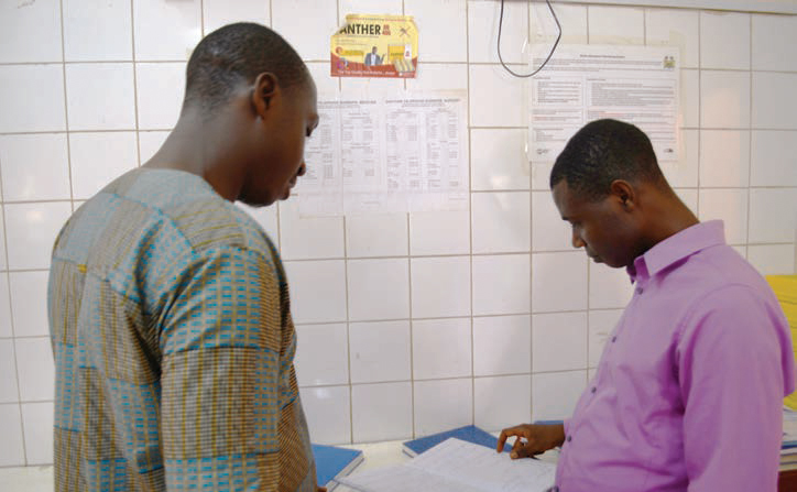 Photo of two men looking over papers in a clinic.