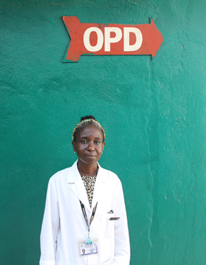 Photo of a female doctor standing underneath a sign that says OPD