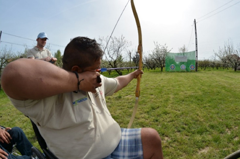 Photo of Marius pointing a bow and arrow at a target.