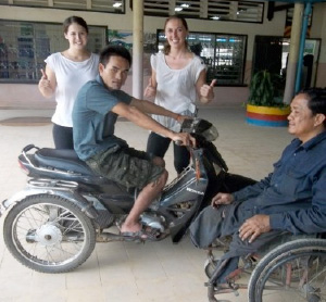 Photo of Hoeun Chan on a motor scooter with two women giving thumbs up in background