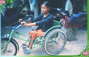 Photo of Hout Thoeung in a wheelchair modified into a tricycle