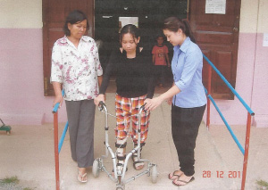 Photo of Ros Sokhom using a wheeled walker flanked by two women