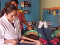 Photo of Andrea Monroy working on the leg of a young patient