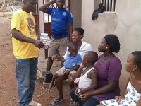 Photo of Nana Ohene Kwatia talking to members of a household outdoors