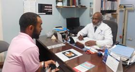 Photo of William speaking with a doctor across a desk