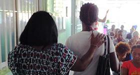 Photo of a navigator leading a woman through a clinic