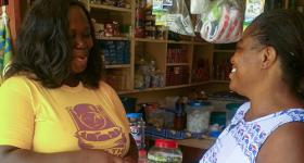 Photo of HealthKeeper Getrude Kofie speaking to a shopkeeper.