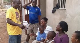 Photo of Nana Ohene Kwatia speaking with people outside their home.