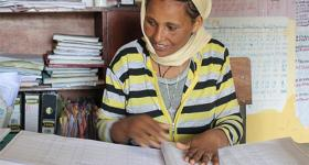 Photo of Alemnesh Assefa at work at a desk