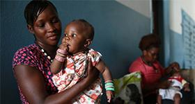 Photo of a woman holding an infant at a clinic