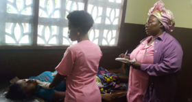 Head nurse Margarete Anthony, right, and colleague at the Sussex community health unit attend to a patient.