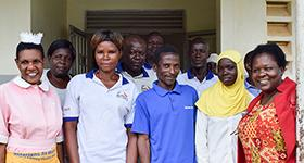 Photo of WellShare's program manager with clients, midwives, and VHT members at Niabiri HCII in Iganga District.