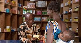 Photo of a woman and child in a drug shop with operator at the counter