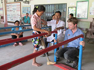 Photo of Sum Srey Norng learning to walk with her prosthetic
