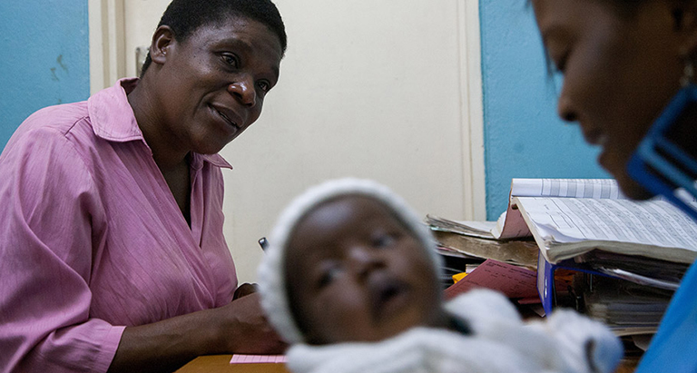 Photo of a community health worker counseling a mother and child at a desk.