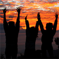 Photo of people with their arms raised at sunset