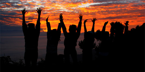 Photo of youth jumping with their hands raised up in silhouette against a setting sun