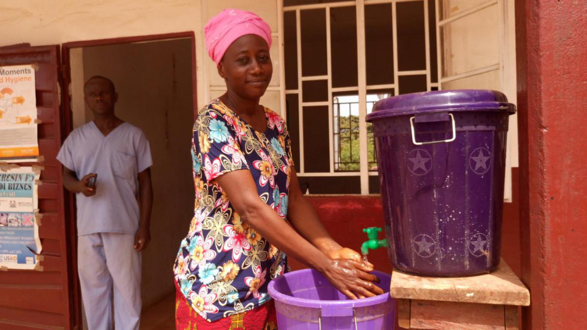 Zainab Fonafah washes her hands in front of the health facility.