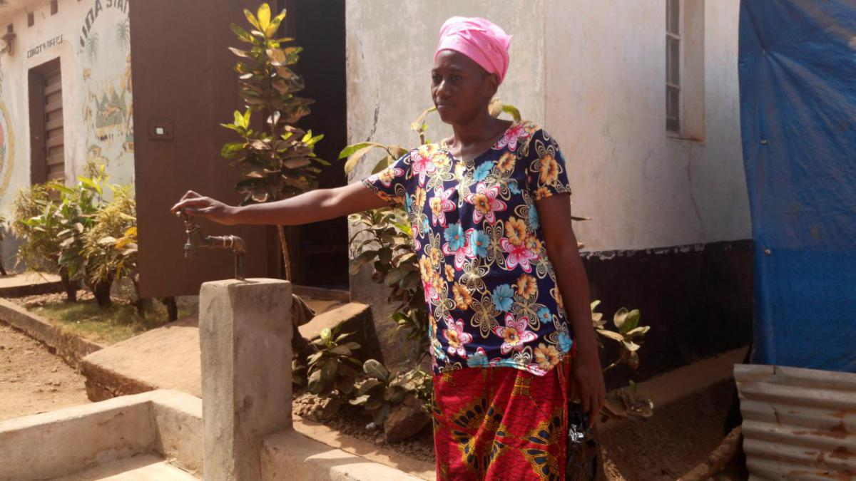 Zainab and one of the taps in her community.